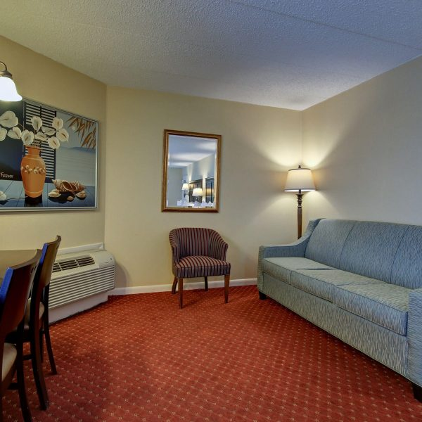 Hotel living room with couch and large painting on the wall