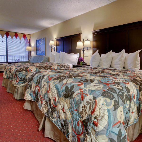 large oceanfront hotel bedroom with 2 large beds and balcony access