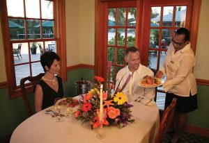 well dressed seated couple being served world/caribbean fusion cuisine