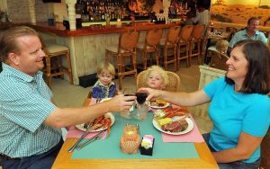 seated smiling family enjoying meal