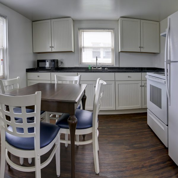 cottage full kitchen with cabinets and 4 seat dining table