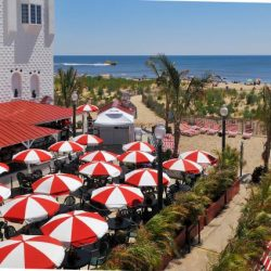 bar and grill on ocean city beach with red and white umbrellas on tables and palm trees