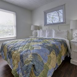 Cottage bedroom with large bed under floral blanket on hard wood floors and next to white walls