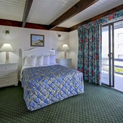 Hotel bedroom with private balcony with floral blanket on bed and floral curtains on window