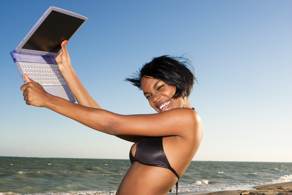 Smiling young woman with laptop at the beach