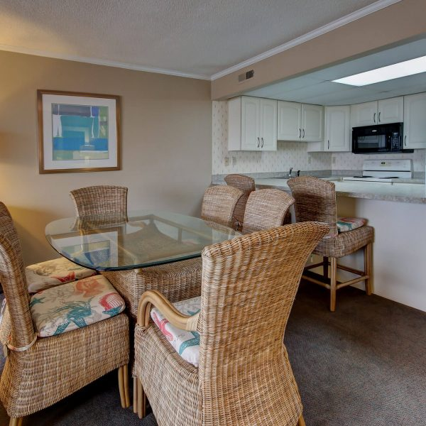 condominium dining area with table, wicker chairs, counter, and full kitchen