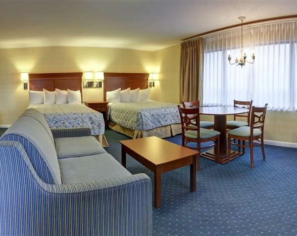 studio suite hotel room with 2 queen beds and living area