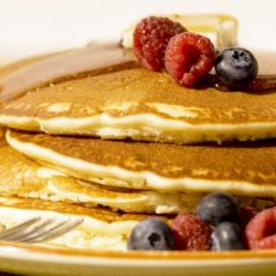 stack of pancakes with raspberries and blueberries and syrup on top